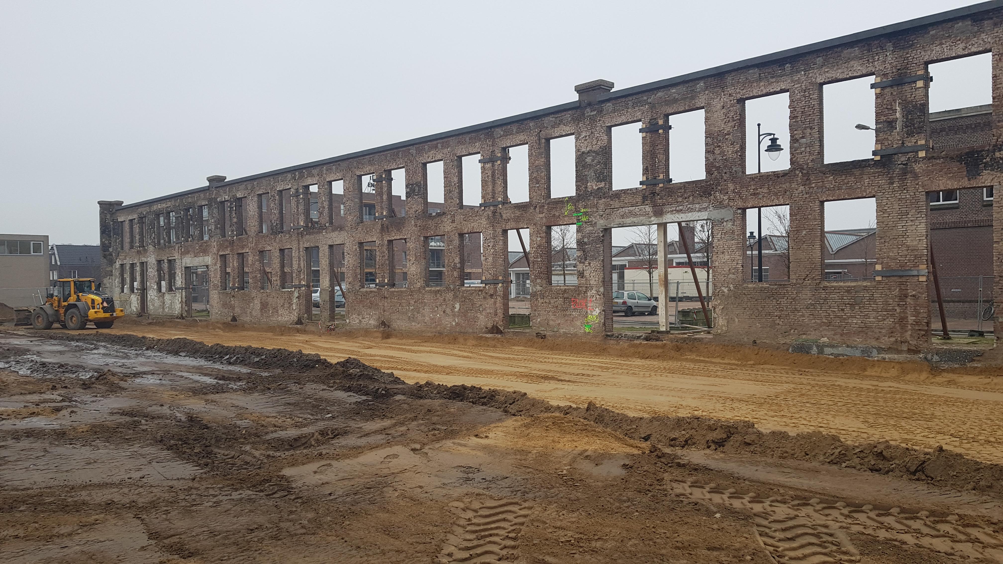 de fabriekshal van Enka is gesloopt; maar de muur is blijven staan. En daartegenaan worden woningen gebouwd